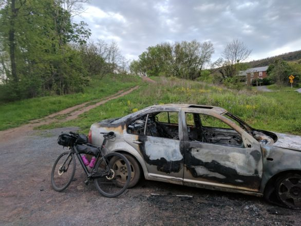 A burnt out car welcomes you to the Abandoned Turnpike.
